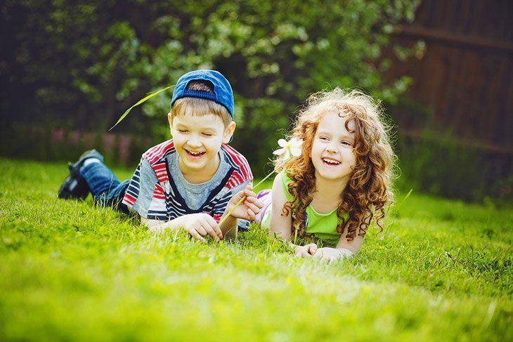 little-girl-boy-lying-on-grassgreen-How-Long-Does-it-Take-to-Grow-Grass