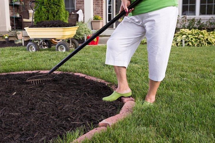 Woman-spreading-mulch-in-garden-how-to-kill-dallisgrass