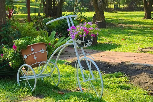 A-lovely-white-metal-bicycle-flower-pot-stand,-in-a-garden-park-in-Bangkok,-Thailand