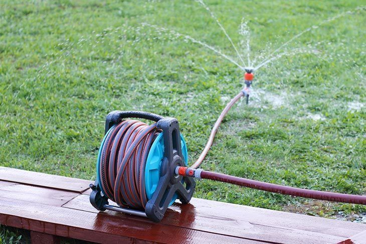 Reel-with-hose-and-sprinkler-in-the-garden-best-garden-hose-reel
