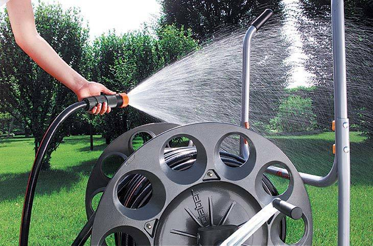 The woman spraying her lawn with some water with a metal hose reel