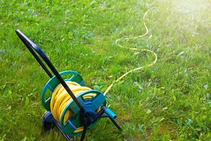 Yellow garden water hose reel cart on a grass lawn