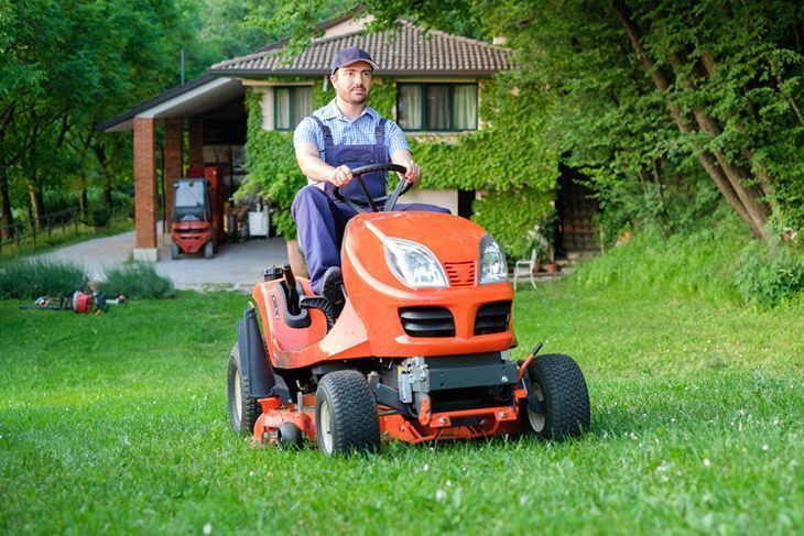 A man operating an electric riding lawn mower